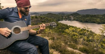 man playing guitar in inspiring landscape