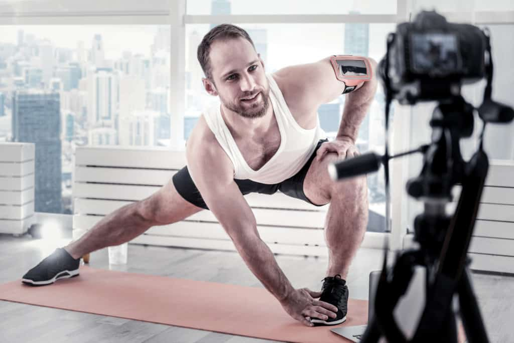 image of male fitness instructor giving online virtual class